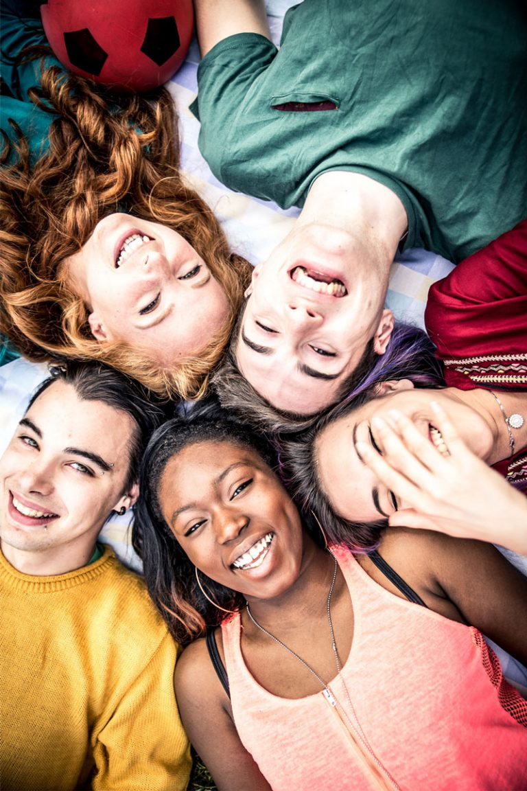 Five young adults in a group, laying on the floor, smiling at the camera while looking up