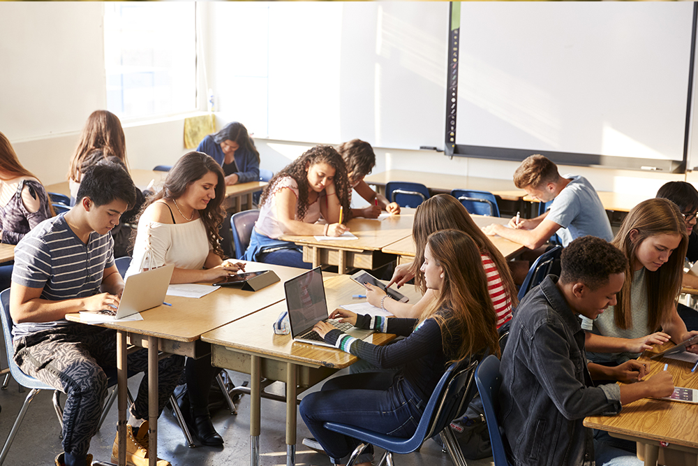 A group of students in class reading, using laptops, and talking.