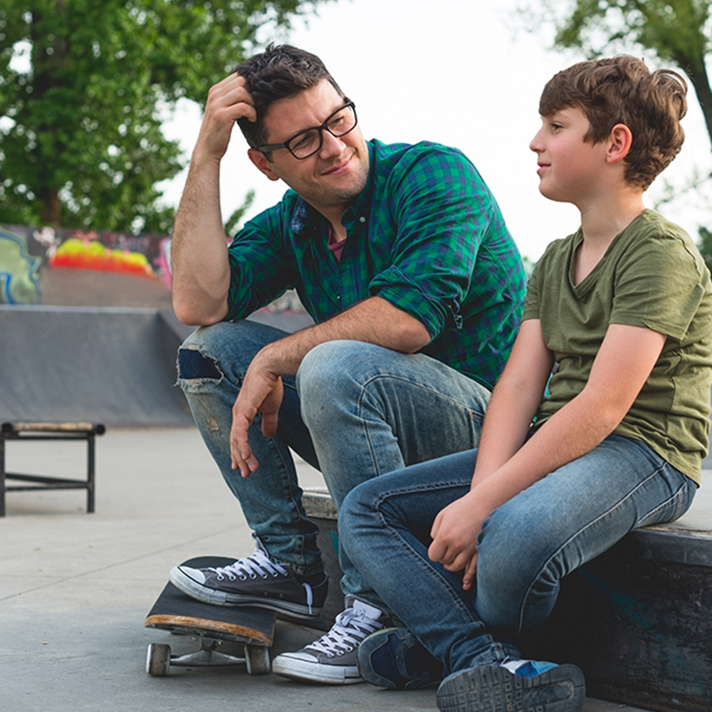 Father and son sitting at a skate park talking